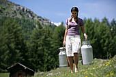 Woman carrying milk cans on alp, Heiligenblut, Hohe Tauern National Park, Carinthia, Austria
