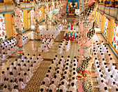 Worshipers at service in the Cao Dai Great Temple. Tay Ninh. Vietnam