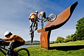 Trialbiker auf einer Eisenskulptur im Park, Linz, Oberösterreich, Österreich