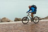 Mountain biker riding along Adriatic Sea coastline, Trieste, Friuli-Venezia Giulia, Italy