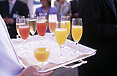 Tray with coctel glasses being offered in a reception
