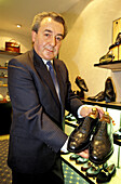 Mr. Brian Jones showing Church s men shoes in his shop. London. England