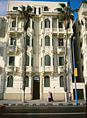 Old 1900 style housing buildings and palm trees at Corniche area. Alexandria. Egypt