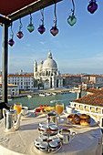 Breakfast on the Grand Hotel Bauer Roof terrace. Ancient palazzeto overlooking Grand Canal and La Salute church. City of Venice. Venetia. Italy