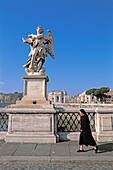 Nun passing by statue of angel at Sant Angelo bridge. Vatican City, Rome. Italy