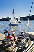 A group of people sitting on a jetty at a lake, sailing boats in the background, Baldeney lake, Essen, Ruhr Valley, Ruhr, Northrhine, Westphalia, Germany