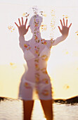 Adult, Adults, Anonymous, Beach, Beaches, Bikini, Bikinis, Color, Colour, Contemporary, Daytime, Exterior, Fabric, Female, Feminine, Figure, Gesture, Gestures, Gesturing, Holiday, Holidays, Human, Knees-up, Leisure, One, One person, Open, Open hand, Open