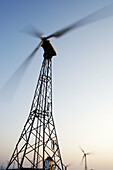 Blurred, Color, Colour, Daytime, Environment, Exterior, Height, Industrial, Industry, Low angle view, Motion, Movement, Moving, Natural resource, Natural resources, Outdoor, Outdoors, Outside, Renewable energy, Spin, Spinning, Tall, Turn, Turning, Vertic