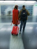 Adult, Adults, Back view, Baggage, Blurred, Color, Colour, Contemporary, Couple, Couples, Female, Full-body, Full-length, Human, Indoor, Indoors, Interior, Luggage, Male, Man, Men, Pair, People, Person, Persons, Platform, Platforms, Public transport, Pub