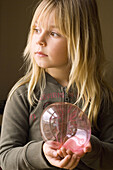 Absorbed, Blonde, Blondes, Caucasian, Caucasians, Child, Childhood, Children, Color, Colour, Contemporary, Daytime, Facial expression, Facial expressions, Fair-haired, Female, Girl, Girls, Hold, Holding, Human, Indoor, Indoors, Infantile, Interior, Kid,