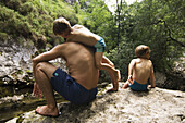 Activity, Adult, Adults, Amusement, Back view, Bathing suit, Bathing suits, Boy, Boys, Child, Children, Color, Colour, Contemporary, Crouch, Crouching, Daytime, Exterior, Families, Family, Forest, Forests, Fun, Holiday, Holidays, Human, Kid, Kids, Leisur