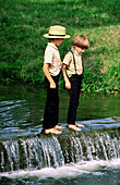 Two amish boys playing in a small river, Lancaster County. Pennsylvania, USA