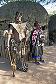 The Chief Biyela dressed with his ceremonial leopard skin and his third wife. Simunye zulu village where visitors can be accomodated in zulu style. Kwazulu-Natal province. South Africa