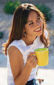 Pretty young woman holding cup
