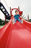 Boy on red sliding board