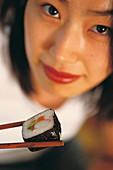 Korean woman eating sushi