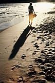 Allein, Alleine, Außen, Barfuss, Barfuß, Eine Person, Eins, Einzeln, einzig, Erwachsene, Erwachsener, Farbe, Frau, Frauen, Ganzkörper, Ganzkörperaufnahme, Gehen, Gehend, Gehende, Hintergrundbeleuchtung, Küste, Meer, Mensch, Menschen, Rückenansicht, Rückl