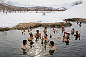 Large groupe of people drinking beer in hot spring in the winter, Kamchatka, Sibiria, Russia