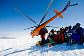 Group of skiers in snow, helicopter in background, Heliskiing, Kamchatka Peninsula, Sibiria, Russia