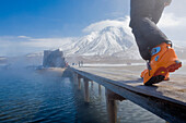 Person wearing ski boots walking over wooden bridge, Kamchatka Peninsula, Sibiria, Russia