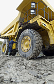 Worker cleaning dumper-truck to carry marl from quarry to cement plant
