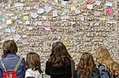 Teen girls looking at writings on courtyard of Juliet s House walls. Verona. Veneto, Italy