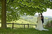 Adult, Adults, Back view, Bond, Bonding, Bonds, Bridal couple, Bride, Bridegroom, Bridegrooms, Brides, Calm, Calmness, Color, Colour, Contemporary, Country, Countryside, Couple, Couples, Daytime, Dress, Dresses, Exterior, Female, Full-body, Full-length,