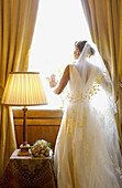 Adult, Adults, Anticipation, Back view, Bridal bouquet, Bridal bouquets, Bride, Brides, Caucasian, Caucasians, Color, Colour, Contemporary, Daytime, Dress, Dresses, Elegance, Elegant, Female, Full-body, Full-length, Hopeful, Human, Indoor, Indoors, Insid