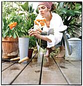 Colour, Contemporary, Crouch, Crouching, Daytime, Exterior, Female, Flower, Flowerpot, Flowerpots, F