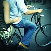 Adult, Adults, Anonymous, Bicycle, Bicycles, Bike, Bikes, Biking, Blue jean, Blue jeans, Boy, Boys, Cities, City, Color, Colour, Companion, Companions, Contemporary, Couple, Couples, Cycle, Cycles, Daytime, Denim, Exterior, Female, Friend, Friends, Frien