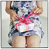 Adult, Adults, Anonymous, Bow, Bows, Box, Boxes, Color, Colour, Concept, Concepts, Contemporary, Dress, Dresses, Female, Gift, Gifts, Human, Idea, Ideas, Indoor, Indoors, Inside, Interior, Knot, Knots, Leg, Legs, One, One person, Open, Opening, Package,