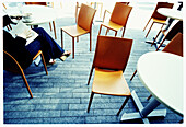 Adult, Adults, Alone, Anonymous, Book, Books, Cafe terrace, Cafe terraces, Calm, Calmness, Chair, Chairs, Coffee, Color, Colour, Contemporary, Crossing legs, Daytime, Exterior, Female, Horizontal, Human, Legs crossed, Leisure, One, One person, Outdoor, O