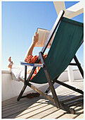Adult, Adults, At home, Back view, Barefeet, Barefoot, Beach chair, Beach chairs, Book, Books, Calm, Calmness, Chill out, Chilling out, Color, Colour, Contemporary, Daytime, Deck chair, Deckchair, Exterior, Feet, Foot, Hold, Holding, Holiday, Holidays, Ho