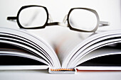 Accessories, Accessory, Book, Books, Color, Colour, Concept, Concepts, Entertainment, Eyeglasses, Glasses, Indoor, Indoors, Inside, Interior, Leisure, Object, Objects, Open, Optics, Page, Pages, Prescription glasses, Reading, Reading matter, Reading matt