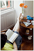 Absorbed, Adult, Adults, At home, Barefeet, Barefoot, Book, Books, Calm, Calmness, Color, Colour, Comfort, Comfortable, Contemporary, Daytime, Female, Flower, Flowers, Full-body, Full-length, Home, Human, Indoor, Indoors, Interior, Leisure, Literature, L