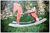 Aged, Childhood, Color, Colour, Concept, Concepts, Daytime, Exterior, Garden, Gardens, Grass, Infantile, Lawn, Old, Old fashioned, Old-fashioned, Outdoor, Outdoors, Outside, Rocking horse, Rocking horses, Toy, Toys, Wood, Wooden, B75-560949, agefotostock