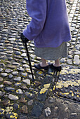 Adult, Adults, Aged, Anonymous, Cane, Canes, Cobble, Cobbles, Coblestone, Coblestones, Color, Colour, Contemporary, Daytime, Detail, Details, Difficult, Difficulty, Elderly, Exterior, Female, Ground, Grounds, Human, Leg, Legs, Mature adult, Mature adults
