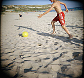 Amusement, Ball, Balls, Beach, Beaches, Color, Colour, Contemporary, Daytime, Exterior, Football, Fun, Holiday, Holidays, Horizontal, Human, Leisure, Outdoor, Outdoors, Outside, People, Person, Persons, Play, Playing, Recreation, Run, Running, Sand, Socc