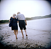 Adult, Adults, Affection, Aged, Back view, Barefeet, Barefoot, Beach, Beaches, Bond, Bonding, Bonds, Calm, Calmness, Coast, Coastal, Color, Colour, Contemporary, Couple, Couples, Daytime, Elderly, Exterior, Female, Fondness, Full-body, Full-length, Holid