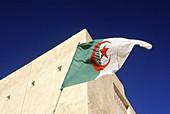Algerian flag on the top of an ancient adobe mosque. Guardaia oasis. Sahara. South Algeria