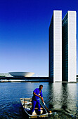 Blue, Blue sky, Boat, Boats, Building, Buildings, Cities, City, Civil architecture, Color, Colour, Contemporary, Daytime, Ethnic, Ethnicity, Exterior, Human, Lake, Lakes, Male, Man, Men, Men only, One, One person, Outdoor, Outdoors, Outside, People, Pers