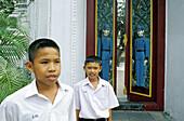 Children at carved gates of Wat Ratchabophit Buddhist temple. Bangkok. Thailand