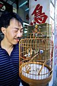Bird lover with his pet. Kowloon, Hong Kong. China