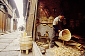 Wood barrels maker at work in the main street. Wushen, small historic city with many canals. Zhejiang province, China