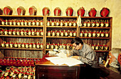 Rice wine and alcohol distillery. The manager doing accounting . Wushen. Zhejiang province, China