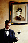 Wine waiter deputy under portrait of Alain Passard s grandmother. Restaurant L Arpege, Rue de Varenne. Owner and chef Alain Passard one of France most acclaimed chefs (three stars in Guide Rouge Michelin). Paris. France