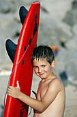 8 year old boy with surfboard on beach, Hendaye. Aquitaine, France