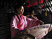 Chinese zither, musicians using traditional instruments to perform in Temple of Eternal Peace, Beihai Park (Beihai Gonggyuan). Beijing, China