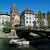 Sightseeing boat and St. Thomas church in background. Strasbourg. France