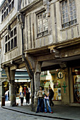 Couple of young tourists and half-timbered houses. Dinan. Britanny. France.
